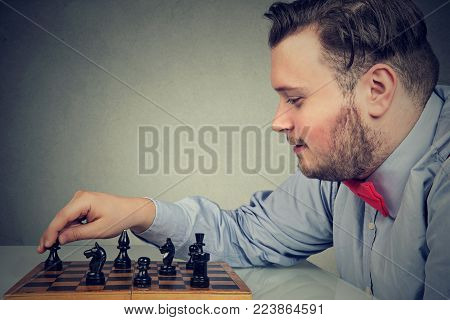 Young chunky man concentrated on building strategy while playing chess.