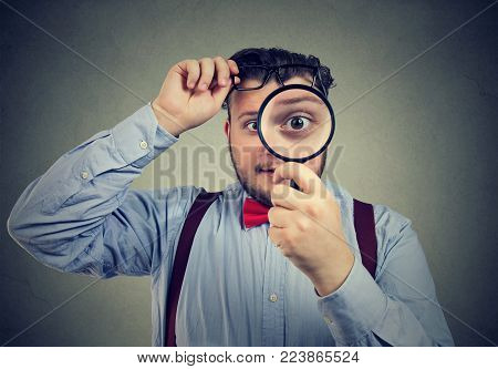 Young chubby man looking at camera curiously through lens of magnifier