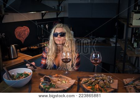 Young woman in sunglass sits in the modern home kitchen at the bar counter with food and wine. Attractive blonde female waiting for a late dinner with her boyfriend and holds smartphone in hand