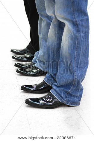 Feet Of Three Men In Black Leather Shoes