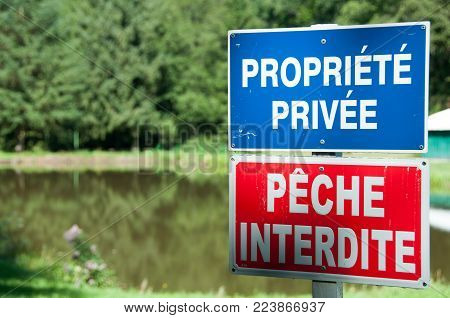 Private property-No fishing- Sign prohibiting fishing at the edge of a lake in France.