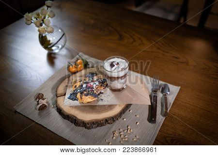 Beautiful dish for breakfast on the stylish wooden tray. Fresh pancakes and parfait with fruits decorated with toppings and nuts on the wooden table. Breakfast at home ready to eat. Close up view.