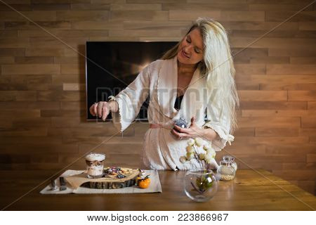 Young woman preparing breakfast on the table in the modern apartment. Attractive blond in bathrobe decorates beautiful dish with fresh pancakes and parfait with fruits on the wooden tray at home.