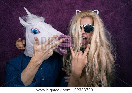 Two funny persons on the purple background shows emotions. Crazy unicorn with expressive young woman in sunglass and kitty ears. Beautiful blonde girl with man from fantasy actively gesticulate