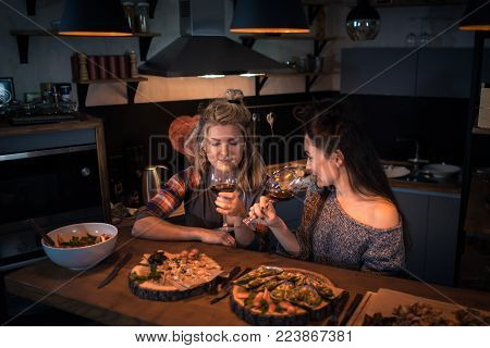Two young women sitting at the table with food and drinking wine in the modern kitchen. Romantic blonde and brunette dinning in the stylish apartment in the evening. Wine testing at home