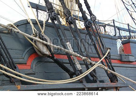 Detail of  mast of  ship. Detailed rigging with sails. Vintage sailing ship block and tackle.