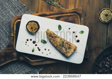 Steak of sea fish halibut with lemon on the grill. Rustic style. Toning. Selected focus. Top view