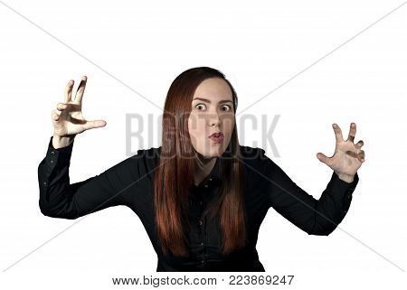 girl on a white background frightens the viewer, taking a menacing pose and making a terrible face