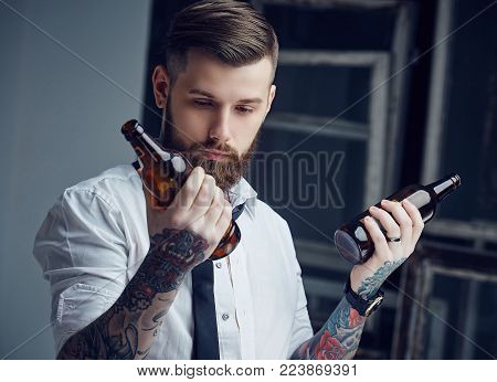 Drunk hipster man with tattoes holding empty beer bottles.