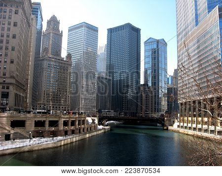 Chicago, IL, winter 2010 - Riverwalk view showing the Chicago River, iconinc buildings on Wacker Dr, and the sidewalks covered in snow on a sunny day.