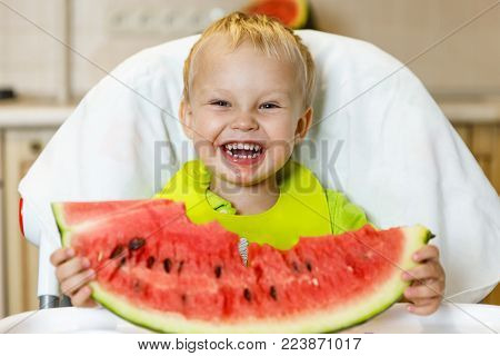 Happy baby eating a slice of a sweet delicious watermelon. Kid biting from a piece of watermelon and getting pleasure.