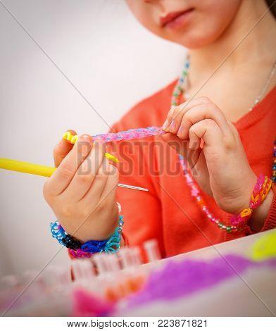 Girl Weaves Jewelry Bracelet Gum, Gum Weaving, Hobby On A Light Background