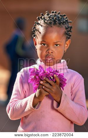 African girl in the yard of a village, Botswana