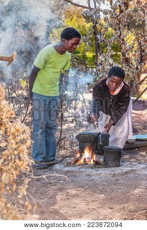 Mom what's for dinner, African woman cooking outdoors kitchen in the village, Botswana