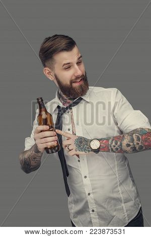 Bearded man in white shirt holding beer bottle. Isolated on grey background.