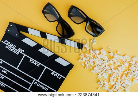 Cinema minimal concept. Watching film in the cinema. 3d glasses, popcorn, clapper board on yellow background