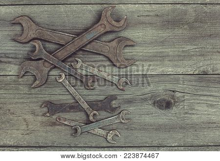 In the old wooden cracked the working surface in the workshop lie in the left corner of the vintage used rusty discolored steel metal dirty wrenches of different sizes.