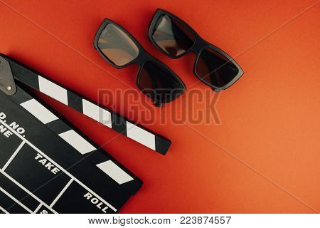 Cinema minimal concept. Watching film in the cinema. clapper board, 3d glasses, on red background.
