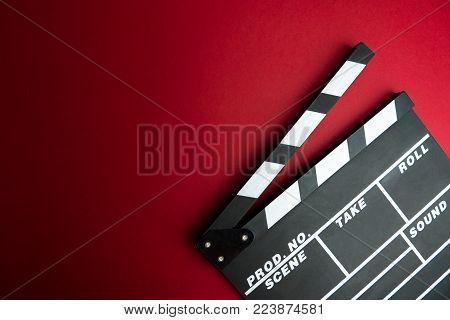 Cinema minimal concept. Watching film in the cinema. clapper board on red background. Screenwrite desktop