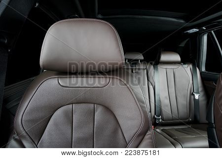 Modern luxury car  brown perforated leather interior. Part of  leather car headrest seat details. Back seats in background