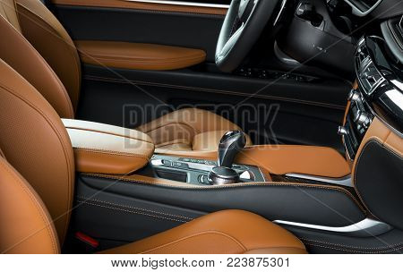 Modern luxury car Interior - steering wheel, shift lever and dashboard. Car interior luxury. Beige comfortable seats, steering wheel, dashboard, speedometer, display. Orange perforated leather.