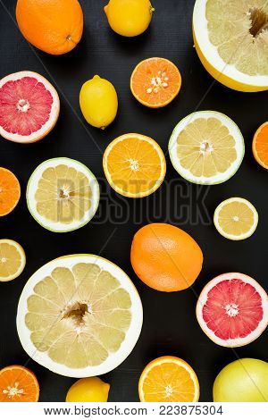 Lemon, orange, mandarin, grapefruit, sweetie and pomelo on black background. Flat lay, top view. Fruit background