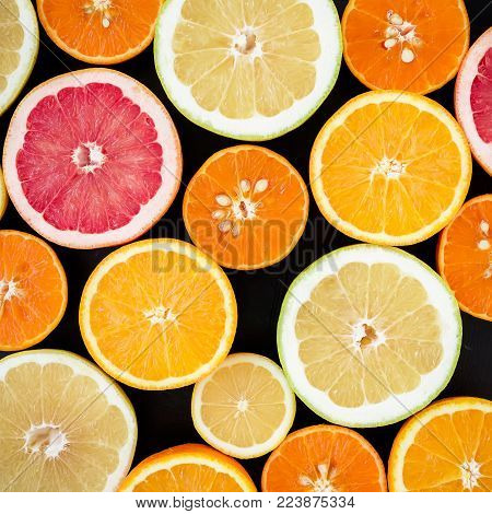 Lemon, orange, mandarin, grapefruit, sweetie and pomelo on black background. Flat lay, top view. Fruit colorful background