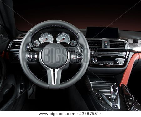 Modern luxury car Interior - steering wheel, shift lever and dashboard. Car interior luxury.Steering wheel, dashboard, speedometer, display. Red and black perforated leather.
