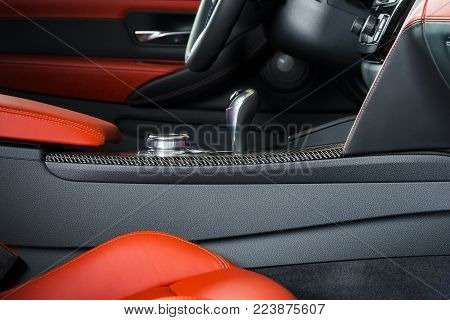 Modern luxury car Interior - steering wheel, shift lever and dashboard. Car interior luxury inside. Steering wheel, dashboard. Red and black leather cockpit