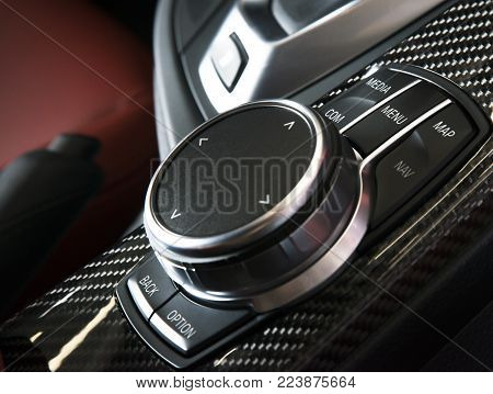 Media and navigation control buttons of a Modern car. Car interior details. Red leather and fiberglass panels interior of the luxury modern car. Modern car interior