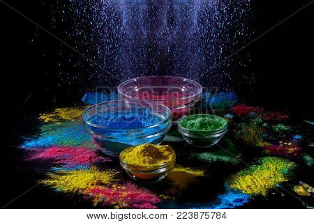 Indian Holi festival colours. Several bowls with Holi paint powder. Explosion of blue color on black background.