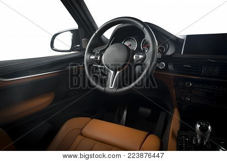 Modern luxury car Interior - steering wheel, shift lever and dashboard. Car interior luxury inside. Steering wheel, dashboard, speedometer, display. Red, orange, peach leather cockpit isolated on white with clipping path.