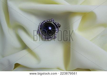 On the crumpled silk fabric is a black female brooch decorated with cubic Zirconia