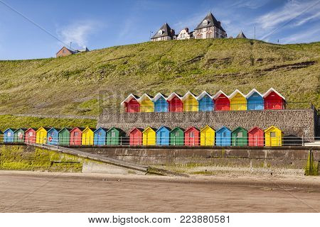 Rows of colorful beach huts on the promenade at Whitby Sands, Whitby, North Yorkshire, England, UK, on a beautiful sunny morning in spring.