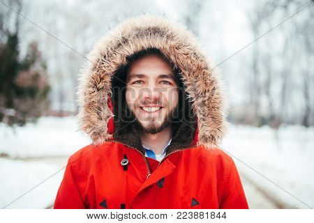 Portrait, close-up of young stylishly man smiling with a beard dressed in red winter jacket with a hood and fur on his head stands against the background of a snow-covered city. Winter and frost theme