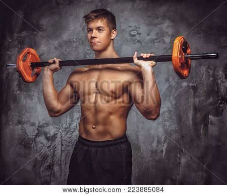 Shirtles muscular young guy holds barbell over grey background.