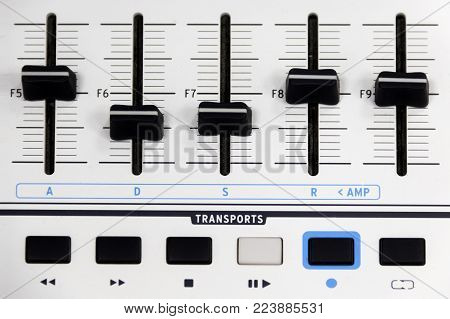 Finger pushing a mixing desk slider shallow depth of field, panel with control buttons