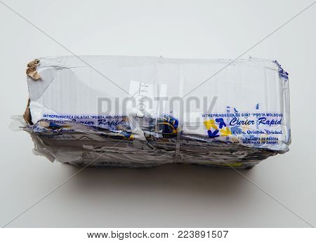 PARIS, FRANCE - JAN 9 2017: Broken parcel covered with safety scotch adhesive band from Posta Moldovei, Moldovan postal service - white table background