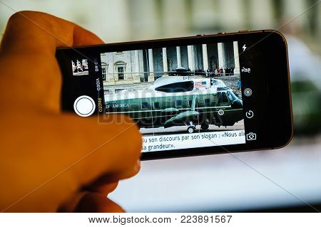 PARIS, FRANCE - JAN 20, 2017: Man watching TV news reporting 45th U.S. President Donald Trump's inauguration ceremony - Obama leaving Capitol by helicopter