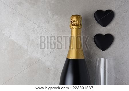 Valentines Day: Black hearts and flute next to an unopened bottle of Champagne.