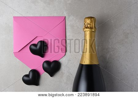 Valentines Day: Pink envelope and black hearts next to a bottle of champagne.