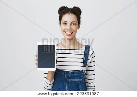 Shot of beautiful brunette girl with two hair buns standing against gray background with joyful smile and showing screen of tablet computer. Excited young female demonstrating new technologies