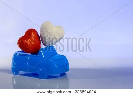 Concept love and auto. St. Valentine's Day for motorists. Honeymoon trip by private transport. Wedding two hearts. Red and white heart in a blue cabriolet car on a light background. Close-up. Toned. Copy space.