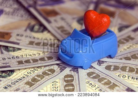 Close-up. Red heart in a blue cabriolet on the background of many hundred-dollar bills. Concept love for money in the car. St. Valentine's Day for motorists. Costs for a honeymoon trip by private transport. A wedding contract. Thousand US dollars.
