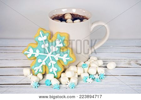snowflake sugar cookies with hot chocolate drink and marshmallows on whitewashed wood