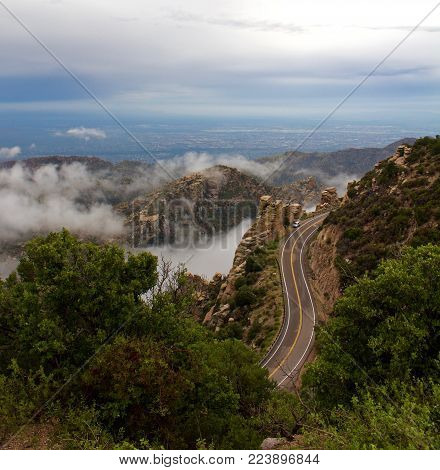 Curvy Mountain Road Winding Around Boulders and forest amoungst Clouds poster