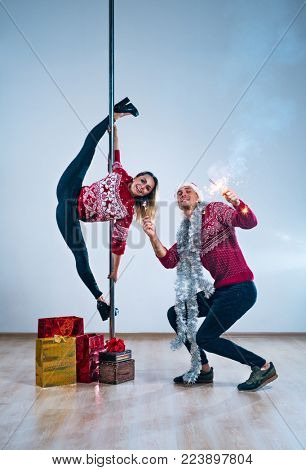Young man and woman pole dancers in winter new year clothing celebrating