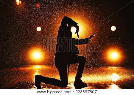 Young man break dancer dramatic silhouette in club with lights and water
