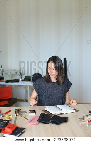 Master received order to make exclusive leather strap for present. Craftswoman with red nails and bracelet on left hand sitting near table with tools in workshop screwing snap in black belt using screwdriver. Concept of handicraft, clothes manufacturing o