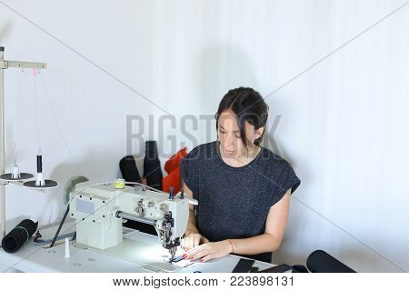 seamstress discuss work with boss using mobile, young pretty woman with ponytail sitting near table with cuttings in workshop and sewing machine talking on phone. Before receiving call female stitching black leather belt. Concept of stylish accessories le
